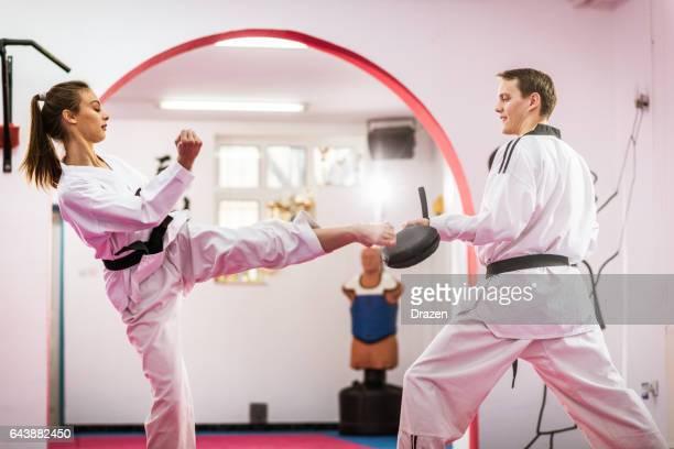 taekwondo feminino jovem entusiasta na formação, aquecendo - taekwondo - fotografias e filmes do acervo