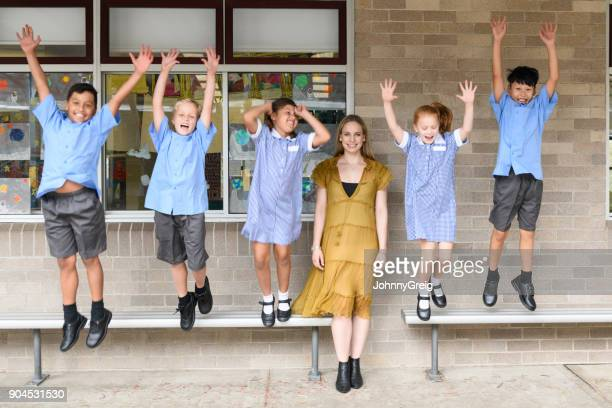 Young female teacher in front of five children jumping and shouting