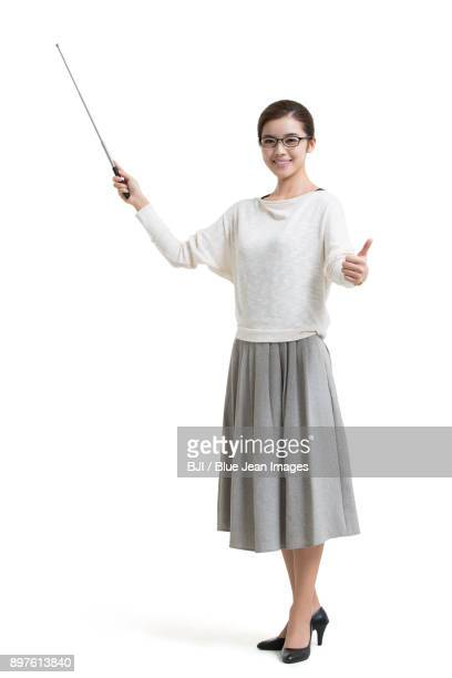Young female teacher with teachers pointer doing thumbs-up
