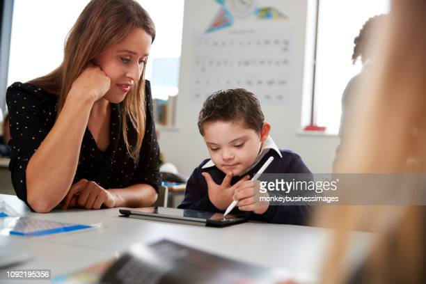 Young female teacher working with a Down syndrome schoolboy sitting at desk in a primary school classroom, selective focus