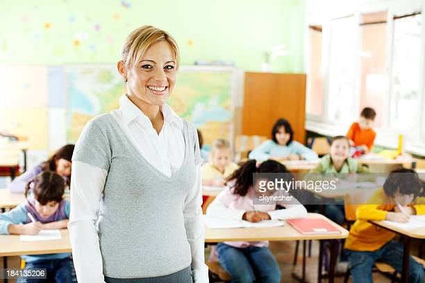 Young female teacher working with pupils in classroom.