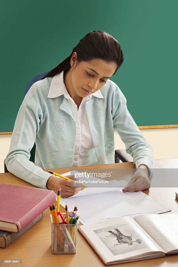 Young female teacher writing on paper at desk in classroom : Stock Photo