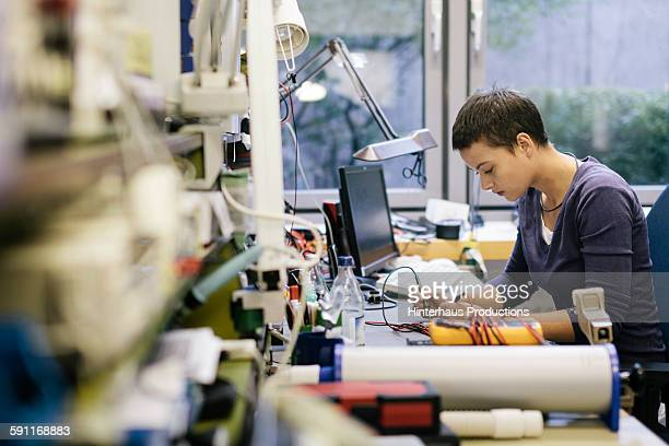Young female technician working on defect device