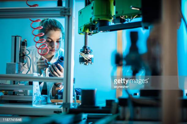 young female technician working with machine parts in a factory. - stem topic stock pictures, royalty-free photos & images