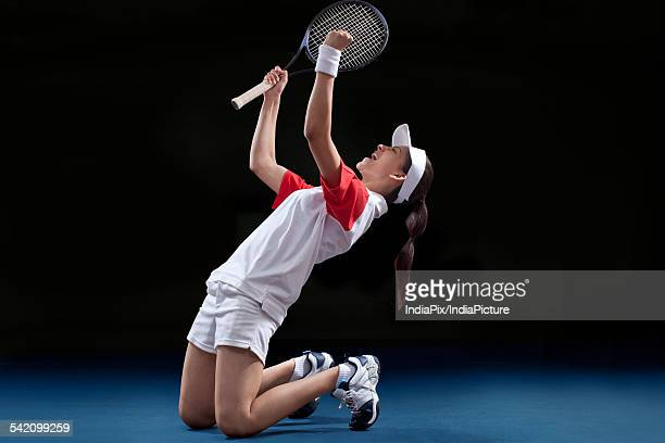 Young female tennis player celebrating victory at court