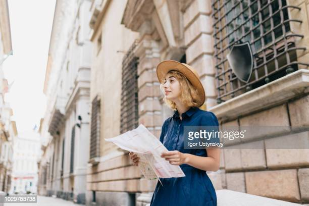young female tourist holding map - mediterranean culture stock pictures, royalty-free photos & images