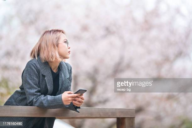 young female tourist holding smart phone and looking at sakura trees - bleached hair stock pictures, royalty-free photos & images