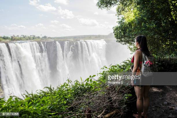 Young female tourist looking out at Victoria Falls, Zimbabwe, Africa