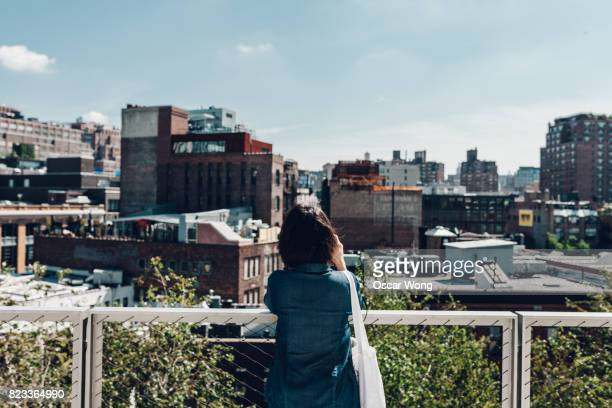 Young female tourist looking out to New York cityscape, on rooftop