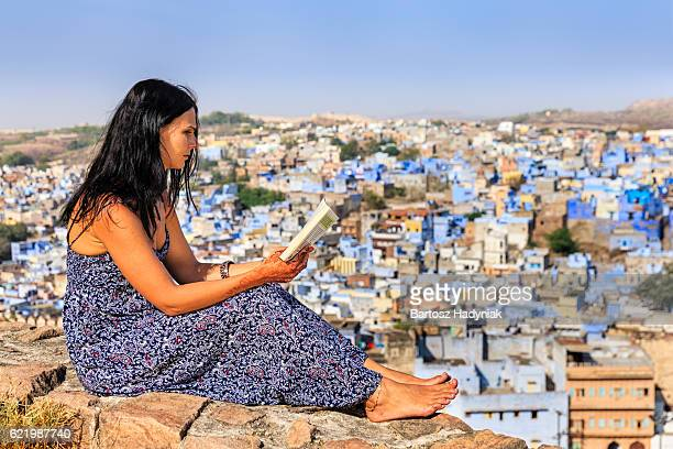 Young female tourist reading book, Jodhpur, India
