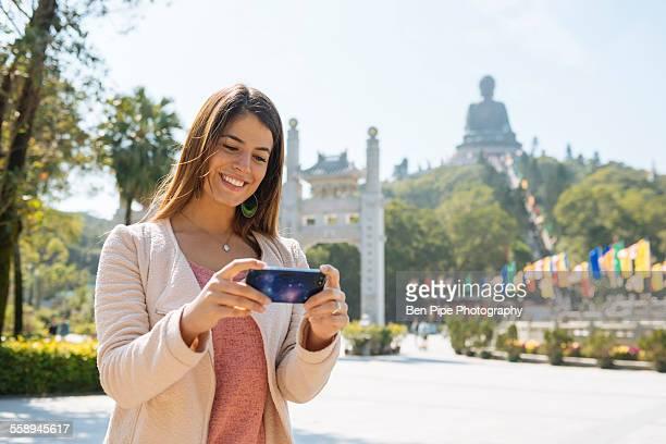 Young female tourist reviewing smartphone photographs in front of Tian Tan Buddha, Po Lin Monastery, Lantau Island, Hong Kong, China