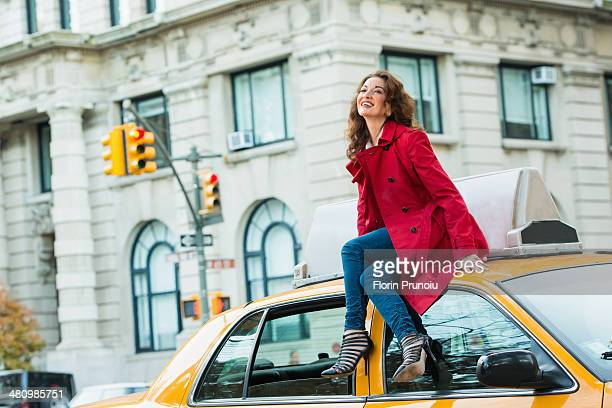 Young female tourist sitting on top of yellow cab, New York City, USA