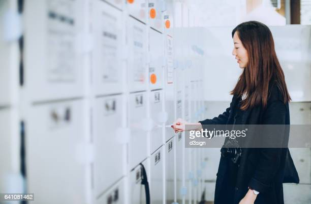 young female tourist storing personal baggages in security lockers - locker stock pictures, royalty-free photos & images