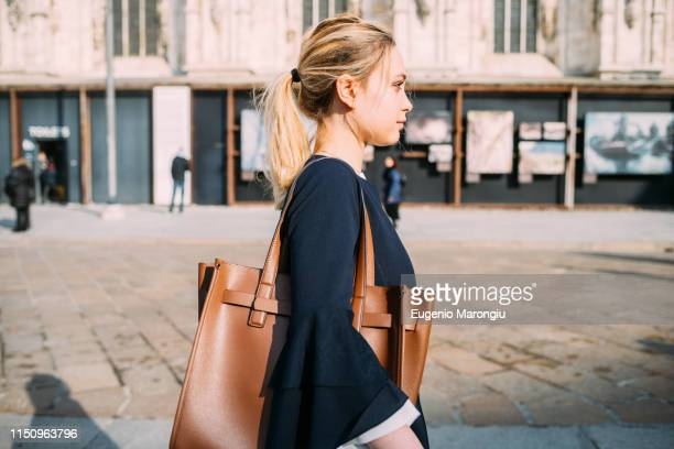 young female tourist strolling and listening to earphones in city street - ショルダーバッグ ストックフォトと画像