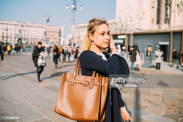 young female tourist strolling and listening to earphones in city square, milan, italy - shoulder bag stock pictures, royalty-free photos & images