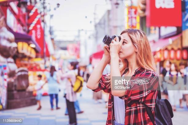 大阪で有名な観光名所の写真を撮る若い女性観光客 - 観光客 ストックフォトと画像