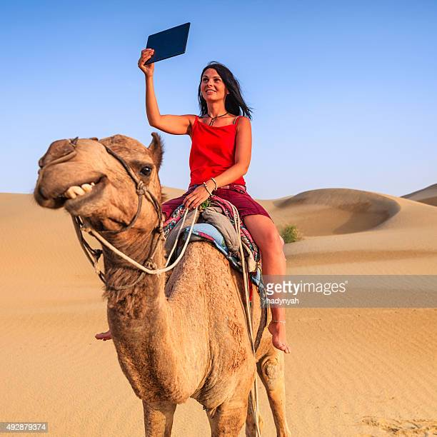 Young female tourist taking selfie on a camel, Rajasthan, India