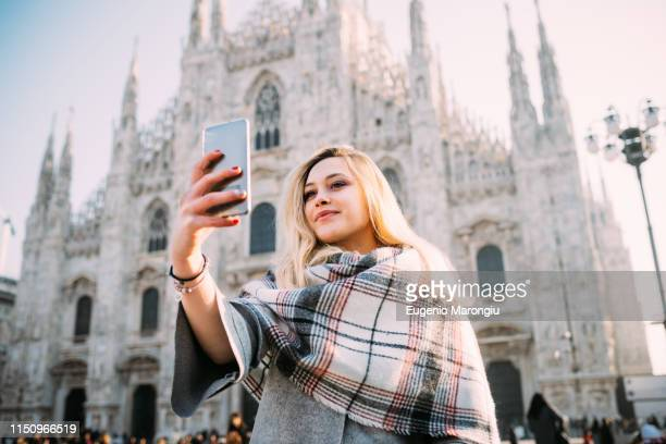 young female tourist taking smartphone selfie in front of milan cathedral, milan, italy - piazza del duomo milano foto e immagini stock