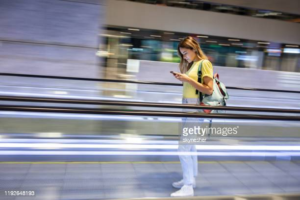 young female tourist text messaging on elevated walkway in blurred motion. - candid forum stock pictures, royalty-free photos & images