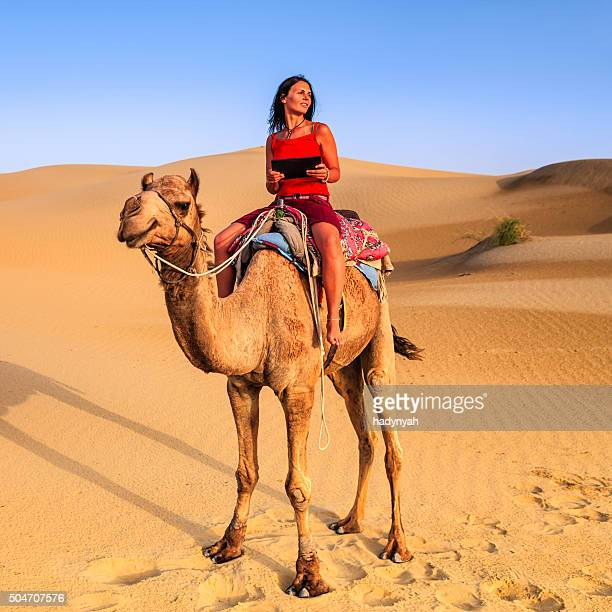 Joven turista usando tableta digital sobre un camello