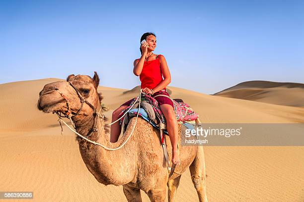 Joven turista mediante teléfono móvil en un camello, Rajastán de India