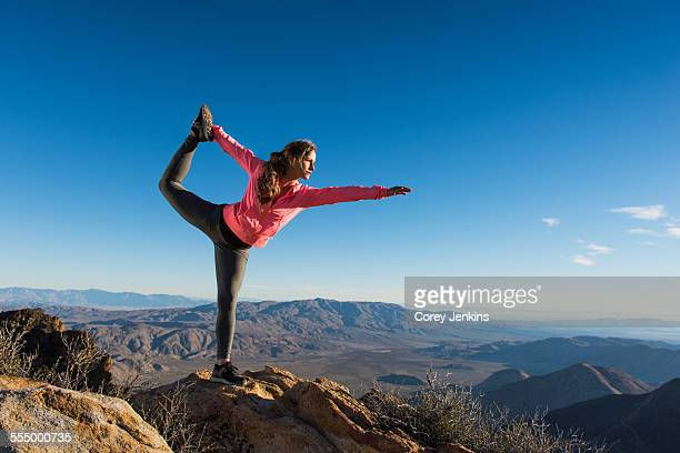 Young female trail runner on Pacific Crest Trail doing yoga whilst looking out over landscape, Pine Valley, California, USA