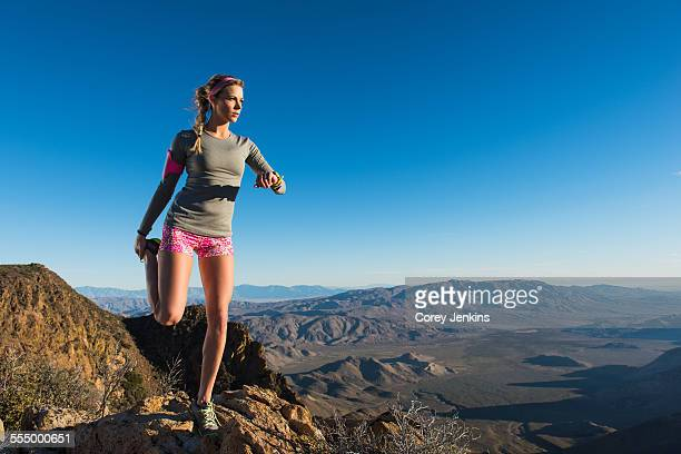 Young female trail runner warming up whilst looking out at landscape on Pacific Crest Trail, Pine Valley, California, USA