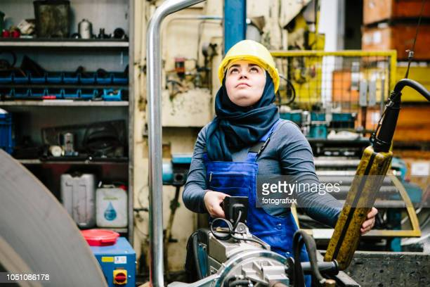 young female trainee transports a welding point pliers with a crane in a workshop - mechanical engineering stock pictures, royalty-free photos & images