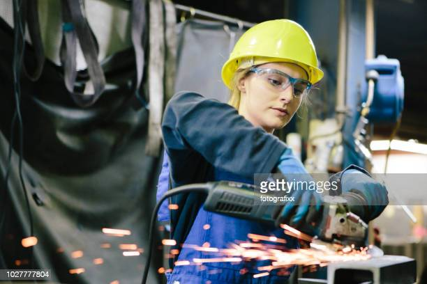 young female trainee welds steel with grinder in workshop