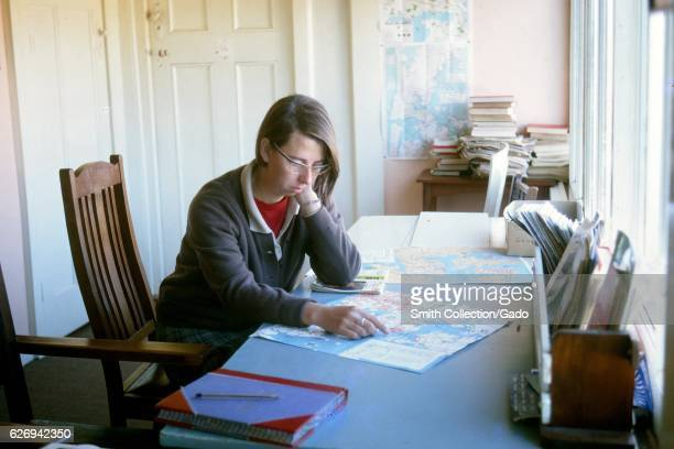 A young female traveler consults maps on a desk at a youth hostel in Auckland New Zealand 1970