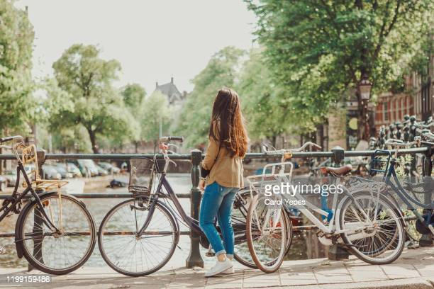 young female traveler exploring amsterdam canals - amsterdam stock pictures, royalty-free photos & images