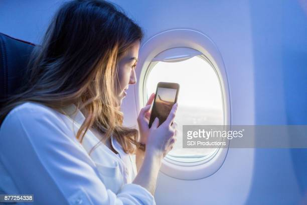 Young female traveler takes picture through airplane window