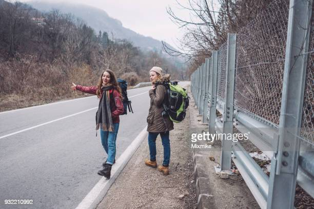 Young female travelers walking on the country road and hitchhiking