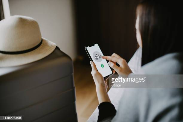 young female traveller lying on bed making car reservations on smartphone in hotel room while on vacation - making a reservation fotografías e imágenes de stock