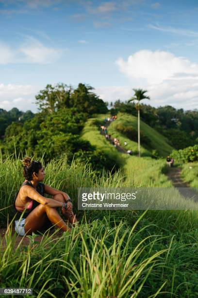 a young female traveller sits with headphones enjoying the countryside view of campuhan ridge walk in ubud, bali, indonesia - christine wehrmeier stock photos and pictures