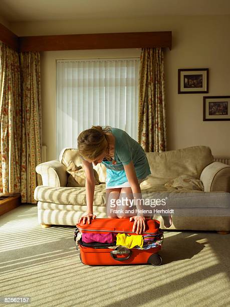 Young female trying to close suitcase