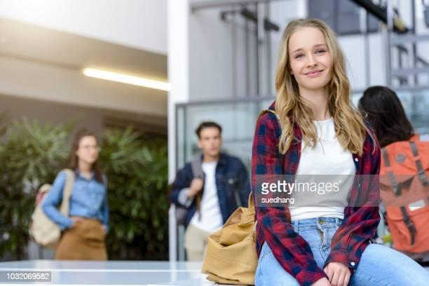 young female university student sitting in university lobby, portrait - student stock-fotos und bilder