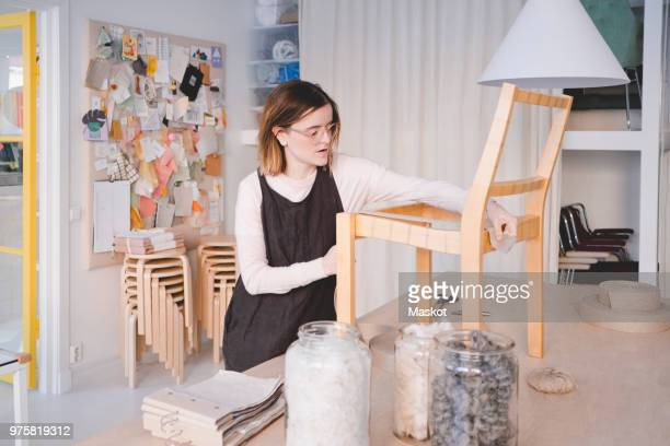 Young female upholstery worker working on chair in workshop