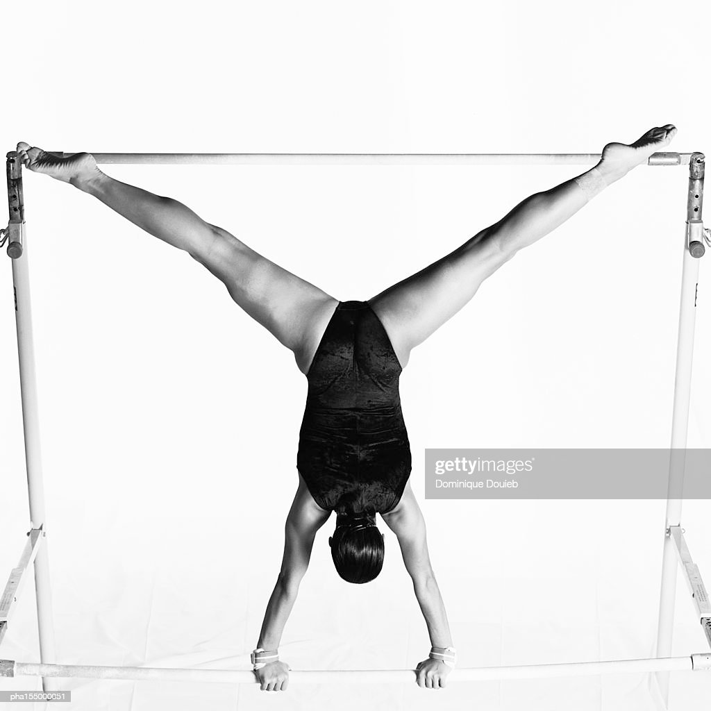 Young female upside down on uneven bars, rear view, b&w. : Stockfoto