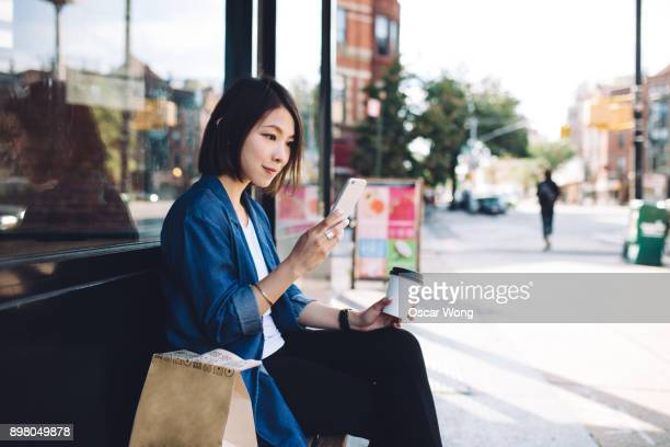 young female using mobile phone outside a cafe in brooklyn - convenience stock pictures, royalty-free photos & images