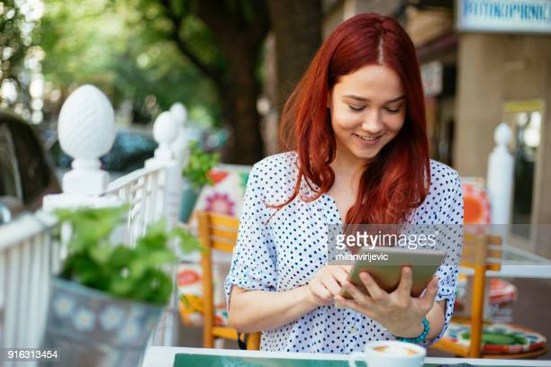 young female using tablet in cafe bar - convenience stock pictures, royalty-free photos & images