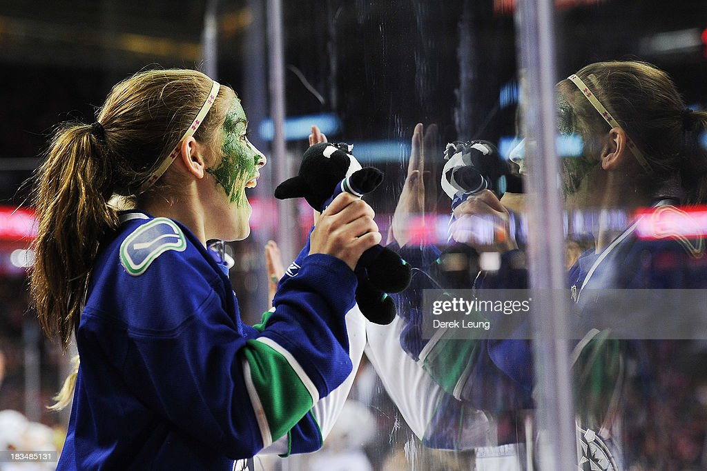 A young female Vancouver Canucks fan celebrates a Canucks goal against the Calgary Flames during the Flames' home opening NHL game at Scotiabank Saddledome on October 6, 2013 in Calgary, Alberta, Canada. The Vancouver Canucks won 5-4 in OT.