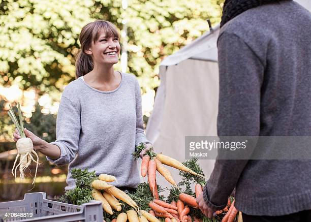 Young female vendor selling vegetables at market stall