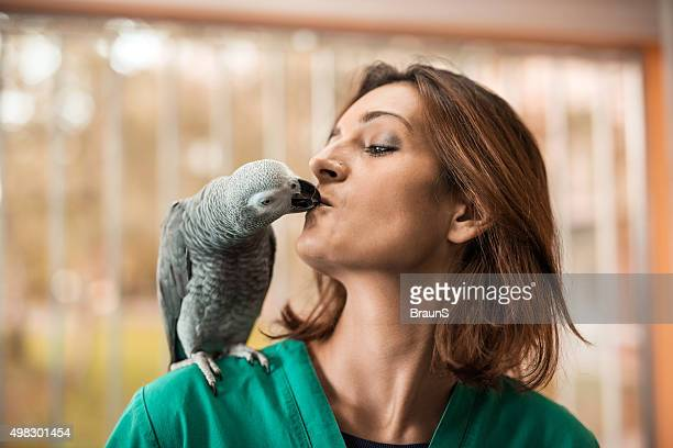 Young female veterinarian kissing with her parrot.