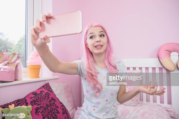 Young female vlogger filming herself on smartphone in bedroom for social media