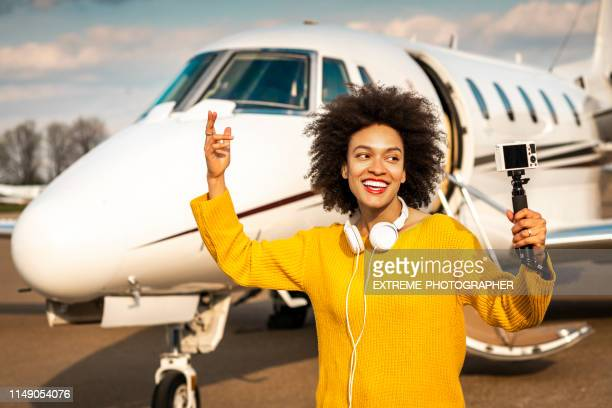 young female vlogger filming herself with her camera mounted on a selfie stick next to a private airplane parked on an airport tarmac - camera icon stock pictures, royalty-free photos & images