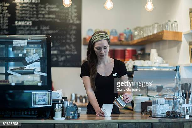 Young female waitress preparing coffee at cafe counter