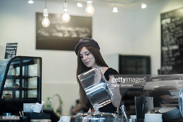 young female waitress selecting cake at cafe counter - sigrid gombert 個照片及圖片檔
