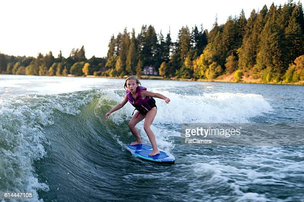 Young female wake surfing behind a ski boat