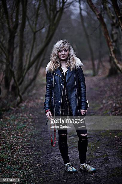 young female walking her dog in woods - black jacket stock photos and pictures
